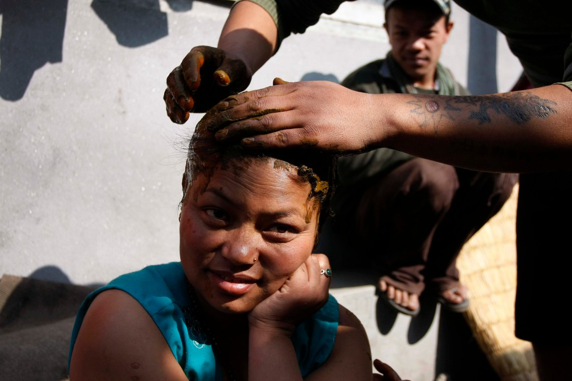 Gayanu Magar's husband is coloring her hair. Her family moved to Kathmandu for better work opportunities and ended up living at the squatter area.