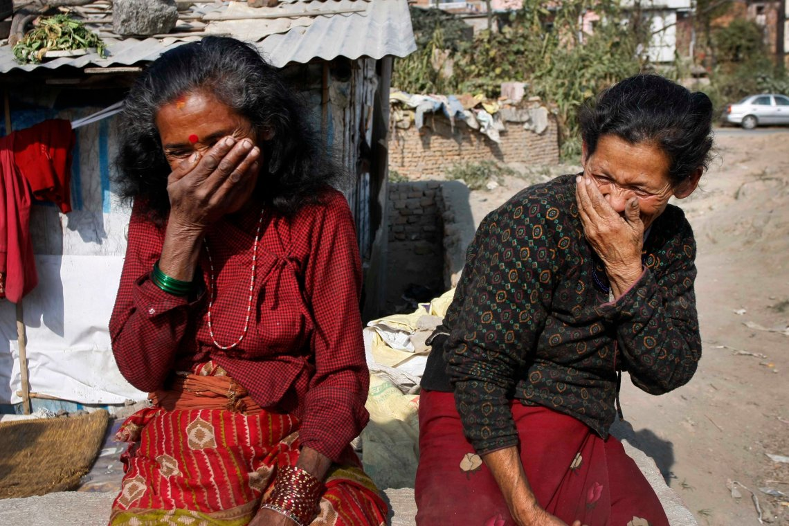 Shova Shrestha(right) and her friend giggle with their hands covering their mouths. Shrestha's house was swept away by a landslide. She lived at several places before moving to Kathmandu.
