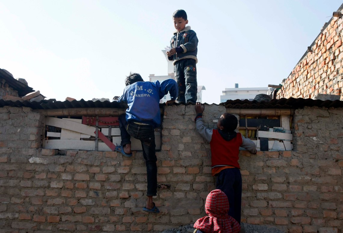 The children play while their parents are at work. Here, they climb the roof of the hut in the squatter.
