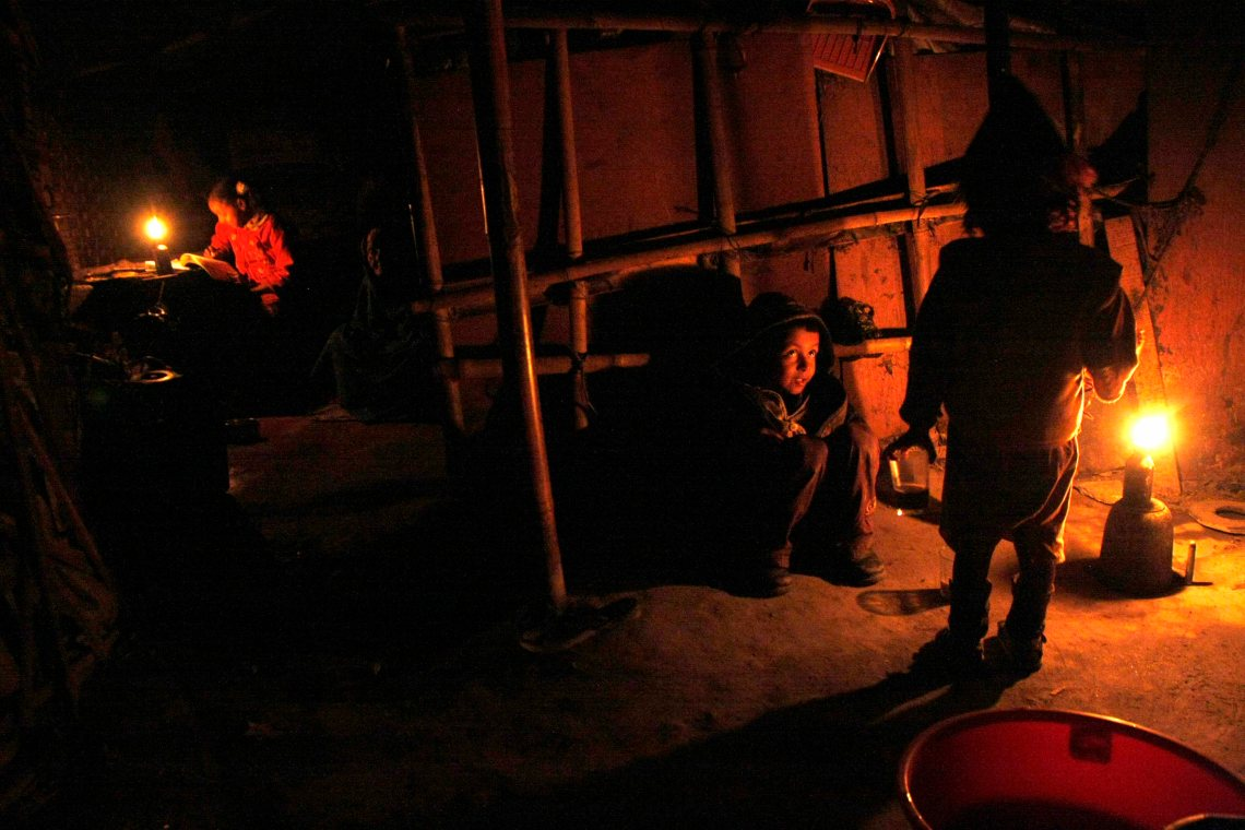 Radha Urau does her homework in the kerosene light while her siblings play.